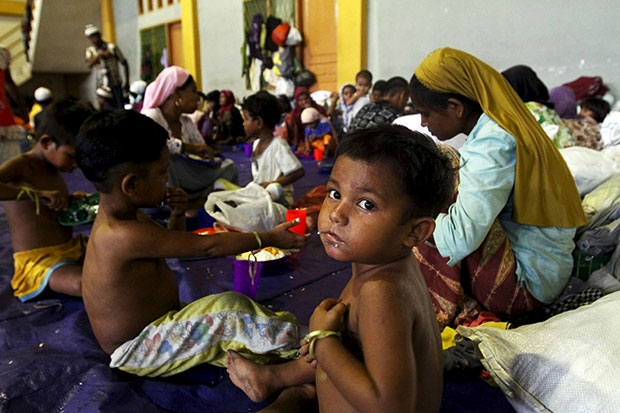 A child, believed to be Rohingya, eats inside a shelter after he was rescued along with hundreds of others from boats in Lhoksukon in Indonesia's Aceh province May 12. There has been a surge in refugees arriving from impoverished Bangladesh and Myanmar to Malaysia and Indonesia following a crackdown on trafficking by Thailand, usually the first destination in the region's people-smuggling network. (Reuters photo)