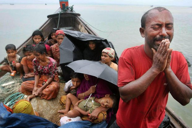 A Rohingya man pleads with authorities as families try to shelter on a typical boat used by migrants to escape the Bangladesh-Myanmar border area. Indonesia and Malaysia have joined Thailand with a policy to refuse asylum to the boat people. (AP file photo)