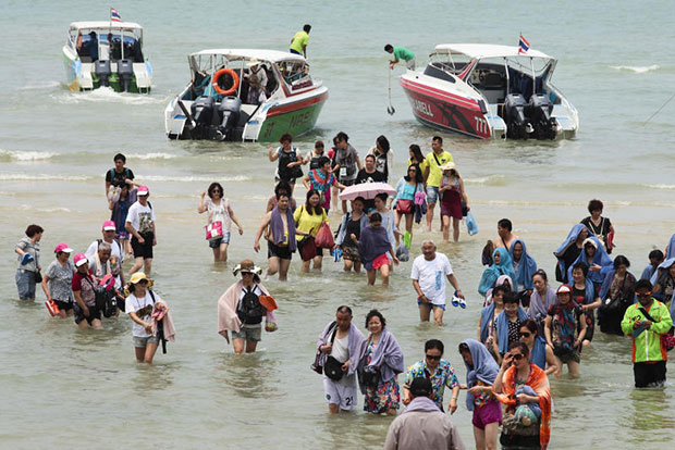 Chinese tourists return to the beach from ferry boats in Pattaya after visiting nearby Koh Lan in Chon Buri. (Bangkok Post file photo)
