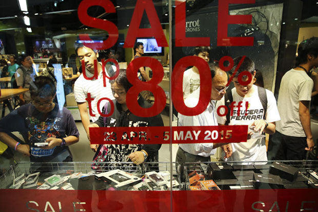 Shoppers select goods at a shop in a department store in Bangkok that offered up to 80% discount in May 2015. (Bangkok Post photo)