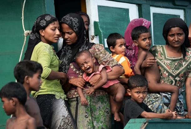 Rohingya migrant women holding children stand on a boat drifting in Thai waters off Koh Lipe in southern Thailand. (AFP Photo)