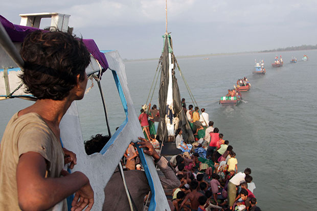 Boats of Acehnese fishermen (in front) tow a boat of Rohingya migrants in their boat off the coast near the city of Geulumpang in Indonesia's East Aceh district of Aceh province before being rescued on May 20. (AFP photo)