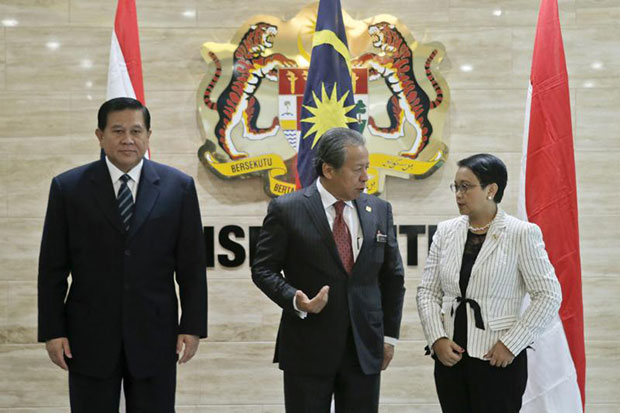 Foreign ministers of Indonesia, Retno Marsudi (right); Malaysia, Anifah Aman (centre), and Thailand, Tanasak Patimapragorn attend a meeting on human trafficking and people smuggling in Putrajaya on Wednesday. (EPA photo)