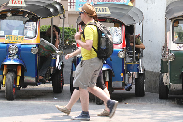 Two tourists stroll past a row of tuktuks waiting for passengers on Rama I Road. (Photo by Somchai Poomlard)