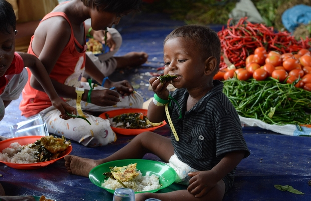 Children eat meals provided by volunteers at a confinement area for migrants in Bayeun on Friday after more than 400 migrants from Myanmar and Bangladesh were rescued by Indonesian fishermen off the coast of Aceh province. (AFP Photo)
