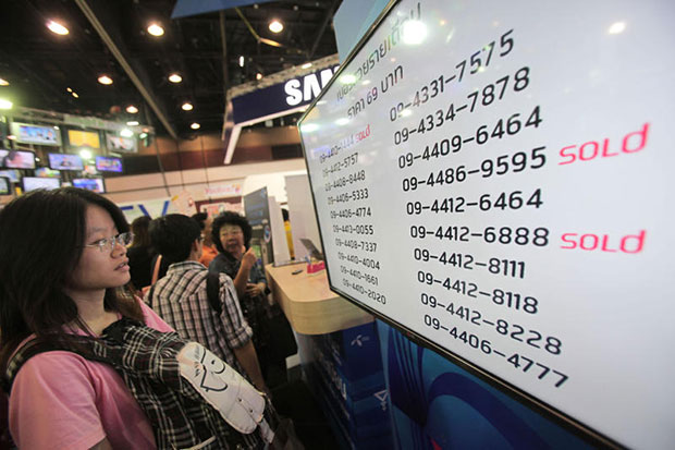 A woman looks at a board showing some offering numbers at a mobile phone fair. (Bangkok Post file photo)