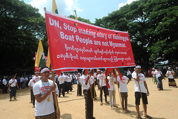 Protesters hold up a banner ahead of a demonstration against Rohingya boat migrants originating from Myanmar in Yangon on Wednesday. (AFP photo)
