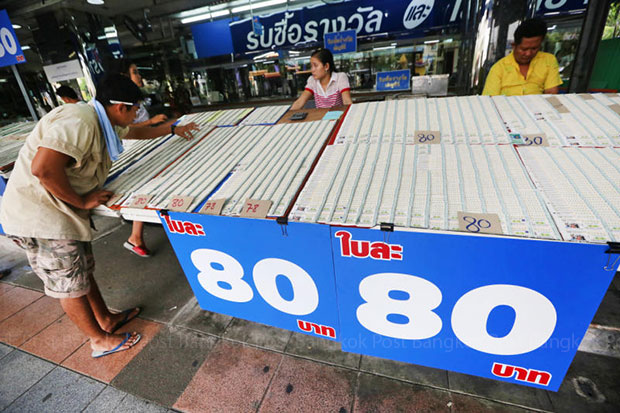 A buyer looks for a lucky lottery number at a stall on Ratchadamnoen Avenue on Wednesday, next to a sign reading 80 baht per pair. (Post Today photo)
