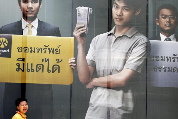 An office worker smiles as she passes a bank advertisement offering savings. (EPA photo)