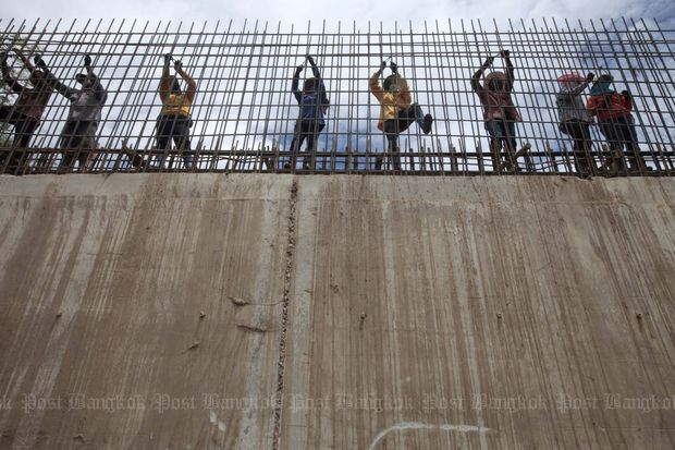 Workers reinforce a nine-metre-high concrete floodwall which stretches for 2km along the banks of the Chao Phraya River in Nakhon Sawan. The great floods in 2011 have prompted the need for an integrated water-management policy. (File photo by Patipat Janthong)