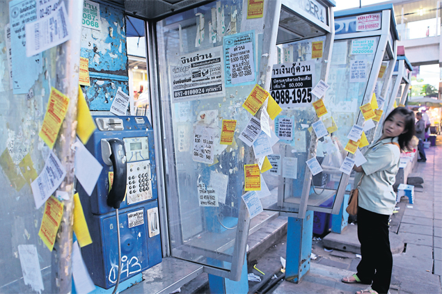 Leaflets advertising low-interest loans litter public phone booths in Bangkok. Rising NPLs have forced debt collectors to work harder. PANUMAS SANGUANWONG