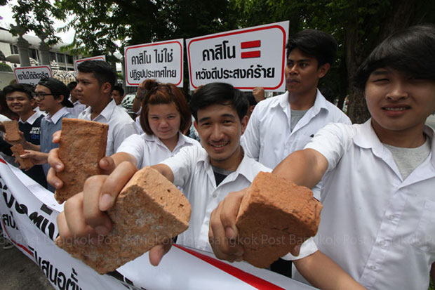 Students show bricks as a symbol of what they think of the push by some National Reform Council members to legalise casinos, at a rally on Thursday in front of parliament. (Photo by Thiti Wannamontha)