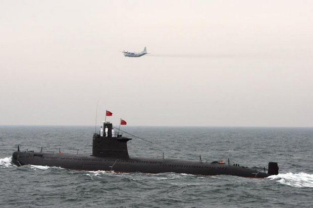 A military aircraft flies past a Chinese Navy submarine at an international fleet review to celebrate the 60th anniversary of the founding of the People's Liberation Army Navy in Qingdao, Shandong province. The Royal Thai Navy reportedly intends to ask the cabinet for funds to buy three Chinese subs for 36 billion baht. (Reuters photo)