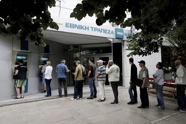 Customers queue to use ATM outside a National Bank of Greece branch in Thessaloniki on Saturday. (Bloomberg Photo)