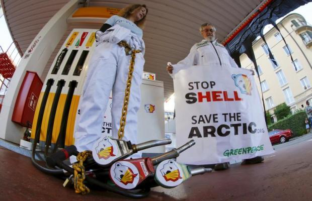 A member of Greenpeace is chained to a gas pump at a Shell gas station during a protest in Zurich yesterday. Greenpeace demands Royal Dutch Shell stop plans to begin drilling for oil in the Arctic.(Reuters photo)