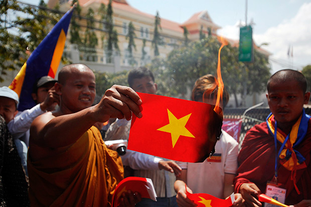 Buddhist monks burn Vietnamese flags made of paper as they join other protesters near the Vietnamese embassy in Phnom Penh in this October photo. Some 250 Cambodian activists, including a lawmaker with the opposition Cambodian National Rescue Party, illegally entered Vietnamese territory in the southern province of Long An over the weekend, the Foreign Ministry in Hanoi said. (Reuters photo)