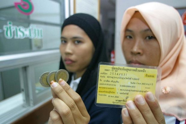 Flashback, 2004: Leela Maero, 22, left, shows three 10-baht coins while Oy Sriboonruang, 21, displays her 30-baht health card, the twin needs to get dental care at Khok Pho district hospital in Pattani province when the 30-baht medical care plan kicked in for the entire country. (Photo by Jetjaras na Ranong)