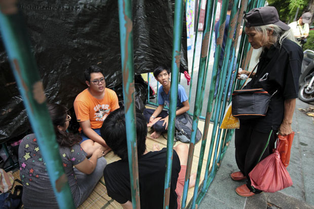 New Democracy Movement activists sit in a mock-up of a prison cell outside Thammasat University to dramatise their call for the release of 14 students jailed for flouting the ban on political gatherings. (Photo by Patipat Janthong)