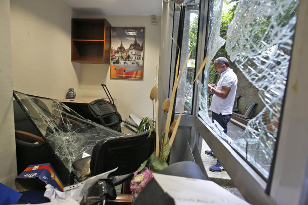 A worker inspects damage at the Thai consulate in Istanbul Thursday. A group of protesters stormed the consulate overnight, smashing windows and breaking in to the offices, where they destroyed pictures and furniture and hurled files out into the yard, to denounce Thailand's decision to deport ethnic Uighur migrants back to China. (AP photo)