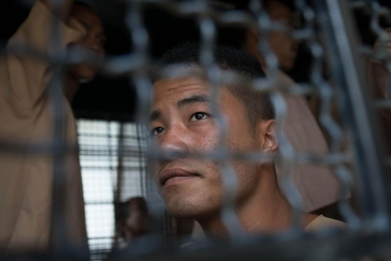 Myanmar national Zaw Lin looks on as he arrives in a prison transport van outside Koh Samui court on the Thai resort island of Koh Samui. (AFP photo)