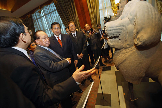 Cambodian Foreign Minister Hor Namhong and Thai counterpart Tanasak Patimapragorn inspect one of the artefacts returned on Saturday. (Photo by Pormprom Satrabhaya)