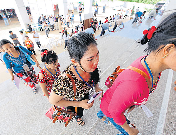 Foreign workers queue up at a one-stop service centre for labour registration in Samut Prakan to apply for temporary work permits.PATTANAPONG HIRUNARD