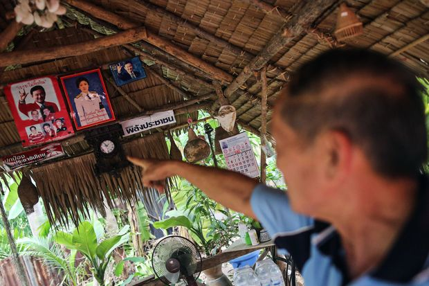 Sakhon Sutasaeng, a retired Agriculture Ministry official, points at posters of former prime ministers Thaksin and Yingluck Shinawatra at his house in Dok Kra Jiew village in Khon Kaen. (Bloomberg photo)