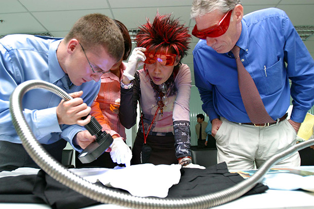 Gregoire Verrier, left, and John McWilliams, right, show Khunying Pornthip Rojanasunan how to use a forensic light source to detect biological evidence -- such as blood, hair or semen -- on a shirt belonging to the late MP Hangthong Thammawattana in this 2003 file photo. Her ruling in that case would lead to her being placed on probation in 2013. (Bangkok Post file photo)