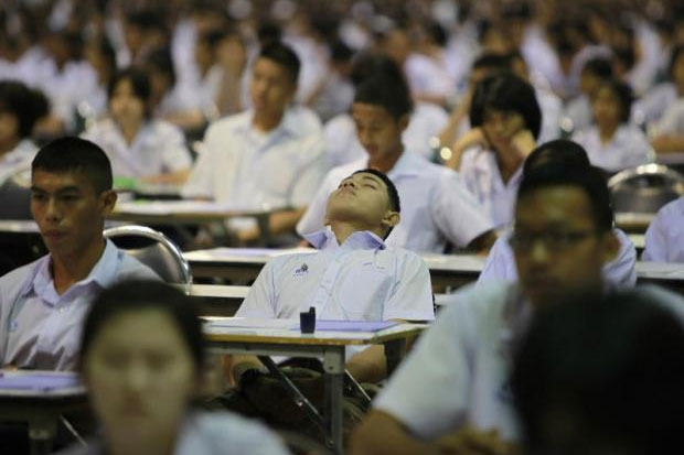 A high school student takes a brief rest during a university admission examination. Thiti Wannamontha