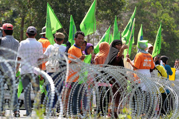 Village opponents of Egat's planned coal-fired power plant in Thepha district gather outside a razor wire barrier in Songkhla on Monday, with only 60 pre-registered people allowed inside to speak. (Photo by Chanat Katanyu)