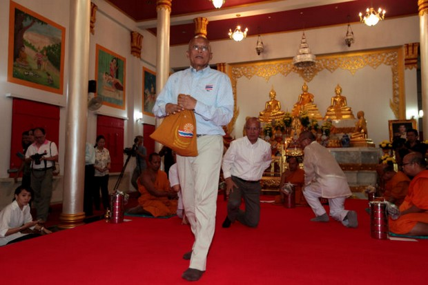Phra Suthep morphs yet again into political activist Suthep Thaugsuban of the People's Democratic Reform Committee (PDRC) Foundation, as he walks away from the ceremony conducted to mark his departure from the monkhood at Surat Thani. (Photo by Chanat Katanyu)