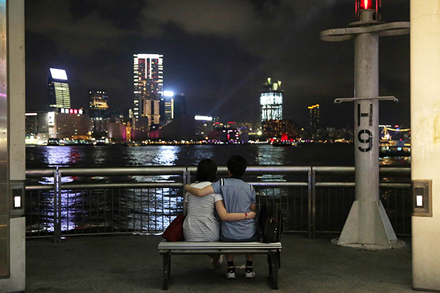 A couple sits and looks at Victoria Harbour in the Central district of Hong Kong. While dating apps developed in the West encourage one-on-one, often no-strings-attached meetings, many in Asia are as much about old-school courtship or friendship in a region where meeting a stranger in a bar can still be a taboo. (AFP photo)
