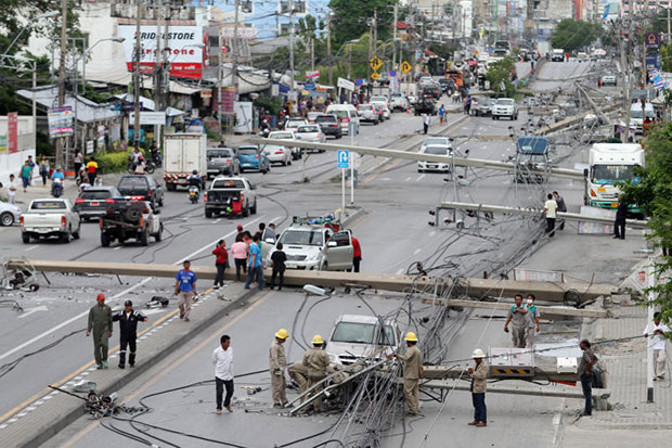 Authorities work to clear Theparak Road in Bang Phli district of Samut Prakan after a tractor-trailer knocked down 47 power poles on Saturday. (Photo by Thanarak Khunton)