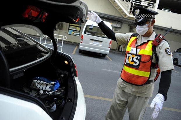 A security guard checks the trunk of a car at MBK shopping centre in Bangkok in April 2015. (Bangkok Post file photo)