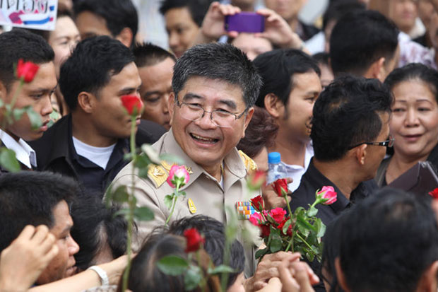 In this March 12 photo public health permanent secretary Narong Sahametapat receives flowers from officials who came to offer  moral support at the ministry following PM's order transferring him to a special adviser post at the PM's Office. (Bangkok Post file photo)