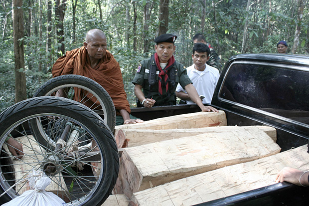 An abbot from Khao Sala temple in Surin's Buachet district inspects Siamese rosewood lumber seized from a group of illegal Cambodian loggers in this 2012 file photo. In the first six months of this year, five Khmer loggers were shot dead and dozens jailed, Phnom Penh says. (Bangkok Post photo)