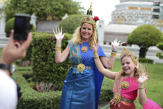 Foreign tourists dressed in rented Thai traditional costumes take a photo at the Temple of Dawn in Bangkok on Saturday. (Photo by Patipat Janthong)