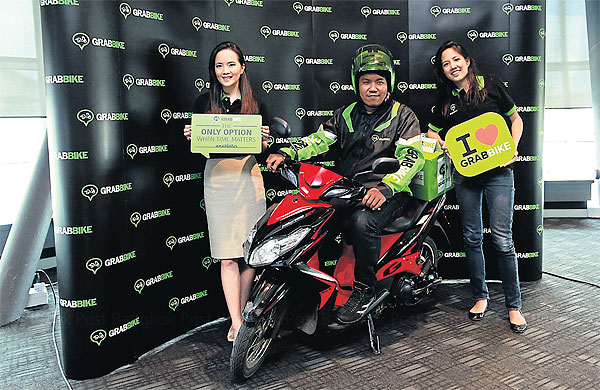 A motorcycle driver is flanked by GrabTaxi's Juthasree Kuvinichkul (left) and GrabBike's Pachara Lawjindakul at yesterday's launch of the new motorcycle service in the Thai capital.