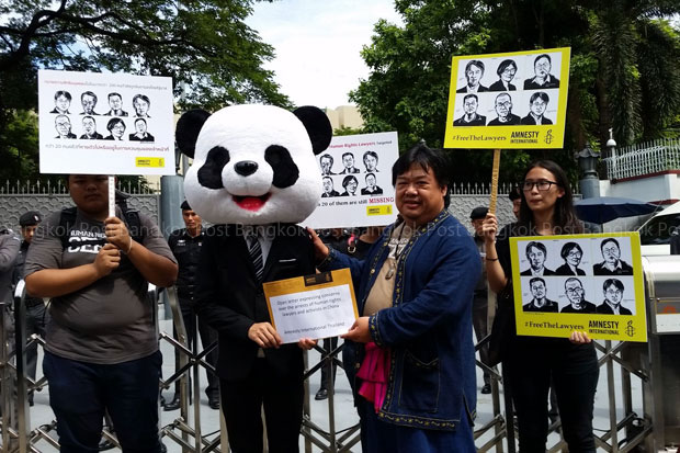 Baramee Chairat, board member of Amnesty International Thailand, pretends to file a complaint in front of the Chinese embassy on Ratchadaphisek Road Thursday morning. (Photo by Achara Ashayagachat)