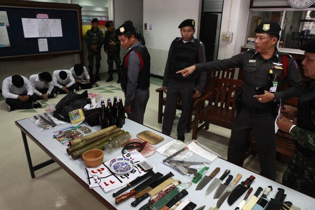 Police officers show an array of weapons and four students from a raid at a vocational college in Bangkok after its students shot and killed a student from a rival college last year. (Photo by Thanarak Khunton)