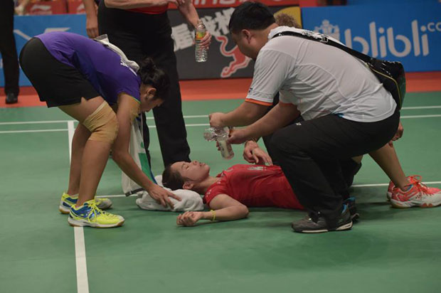 Lindaweni Fanetri (L) of Indonesia puts a towel under the head of Ratchanok Intanon (C) of Thailand after she was injured while playing against her during their round of 16 women's singles match of the 2015 World Championships badminton tournament in Jakarta on August 13, 2015. (AFP photo)