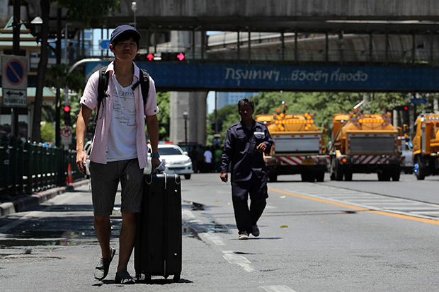 A Japanese tourist walks with his luggage away from the site of a blast at the Ratchaprasong intersection in Bangkok on Tuesday. (Bloomberg photo)