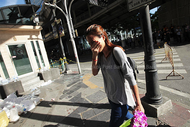 A woman cannot hold back tears on Tuesday as she places flowers at the Erawan shrine blast site. (Photo by Patipat Janthong)