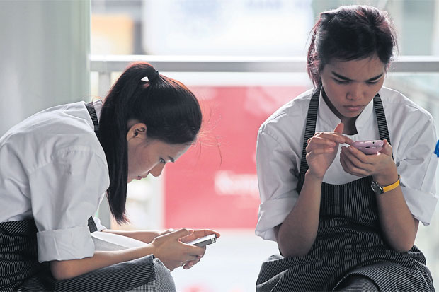 Workers take a break to check their mobile phones. The NBTC has decided not to extend the registration period for prepaid SIM cards, citing security reasons. SEKSAN ROJJANAMETAKUN