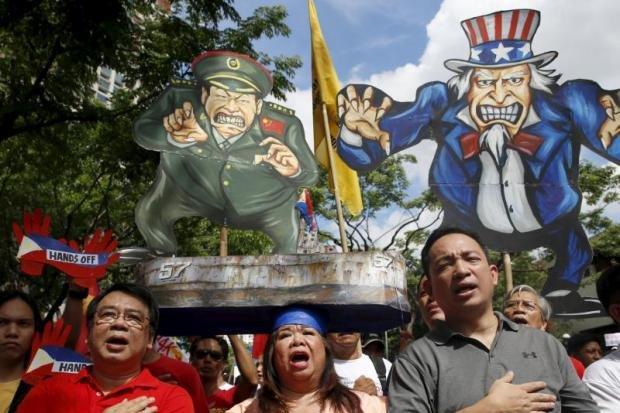 Philippines activists with placards of a Chinese soldier and Uncle Sam head towards the Chinese consulate during a protest in Manila over the South China Sea disputes. (Reuters photo)