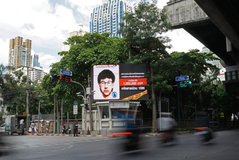 Vehicles pass by a digital billboard showing the sketch of a man suspected to be the Bangkok bomber in central Bangkok. (AFP photo)