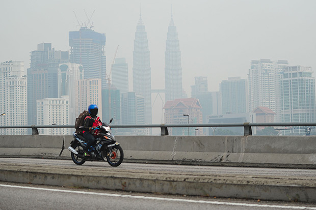 A man rides his bike as Malaysia's landmark Petronas Twin Towers (back centre) are seen obscured by haze in Kuala Lumpur on Aug 24. Four districts located on the southern part of the Malaysian state of Sarawak recorded an unhealthy pollution index due to haze, local media reported. (AFP photo)