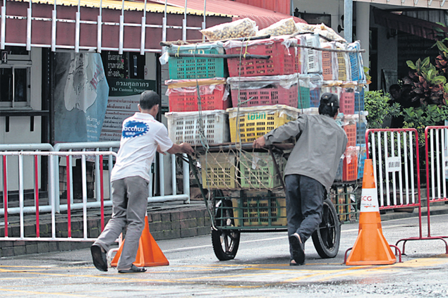 Traders with a cart filled with Thai goods go through Khlong Yai border checkpoint. (Photos By Chanat Katanyu)