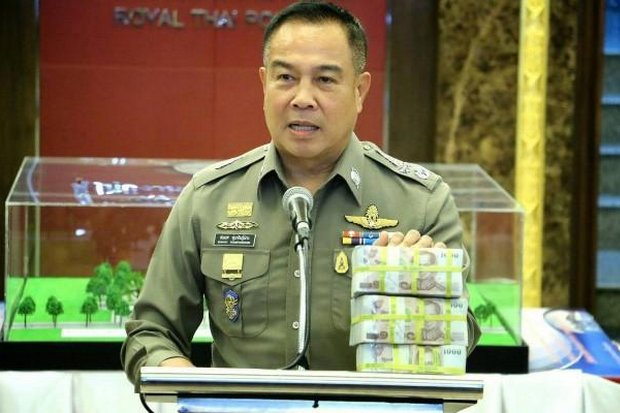 Pol Gen Somyot Poompunmuang shows off what he claims is three million baht, a