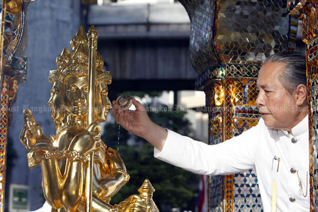 Phra Maharajchakru Sriwisutthikun, Brahmin chief priest, sprinkles holy water on the sacred Brahmin statue during a ceremony on Friday at Bangkok's Erawan shrine. (Photo by Apichart Jinakul)